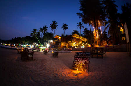 party night: Romantic beach with restaurant and menu with candle lighting at night at Palolem in Goa, India