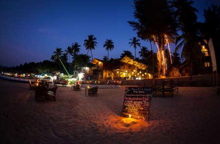 Romantische strand met restaurant en een menu met kaars verlichting 's nachts bij Palolem in Goa, India Stockfoto