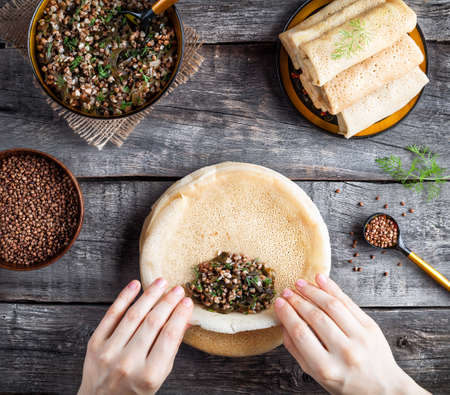 veggies: Woman rolling Russian vegan pancakes with buckwheat and Laminaria served in rustic style on Shrovetide holidays