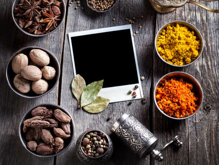 pepper grinder: Spices, pepper grinder, blank photo frame and dry red chili peppers at wooden green background with spoons nearby Stock Photo