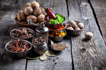 Spezie, macina pepe, un cucchiaio con semi a sfondo grigio in legno