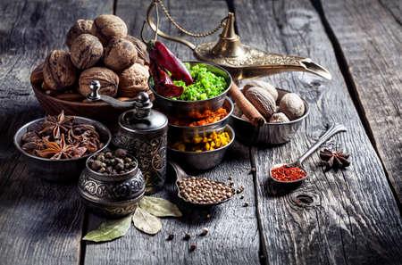 Specerijen, pepermolen, lepel met zaden op grijze houten achtergrond Stockfoto