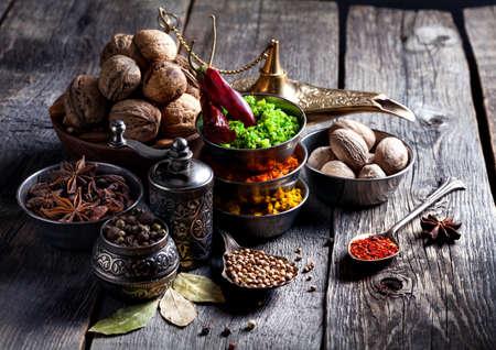 pepper grinder: Spices, pepper grinder, spoon with seeds at grey wooden background