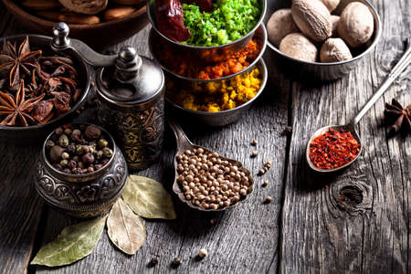 Spices, pepper grinder, spoon with seeds close up at grey wooden background Stock Photo - 55860157