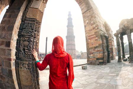 Femme en costume rouge regardant Qutub Minar tour à Delhi, Inde Banque d'images
