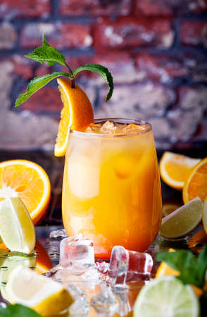 tropicana: Orange cocktail with ice cubes in the tropical bar at brick wall background Stock Photo