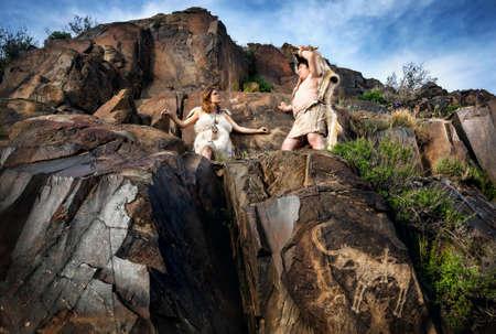 hombre prehistorico: cueva personas vestidos con piel de animal cerca de la antigua dibujo cueva en las rocas