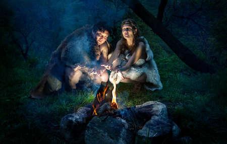 edad de piedra: cueva personas vestidas de animales asan a sí mismo en hoguera en el bosque
