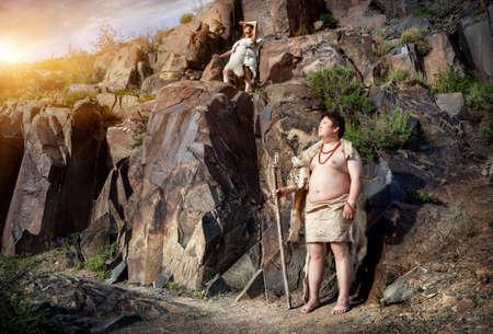 山の中を描く古代洞窟近くの動物の皮に身を包んだ原始的な人々