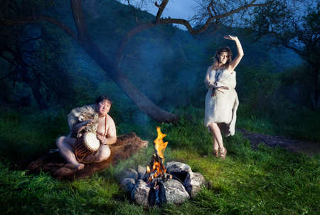 cave dweller: Caveman dressed in wolf skin playing drum and cave woman dancing near bonfire in the forest Stock Photo