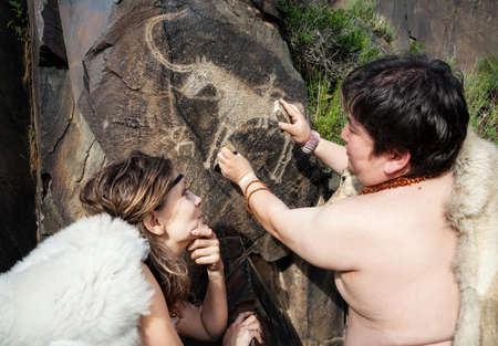 cave dweller: Cave people dressed in animal skin near ancient cave drawing in the rocks