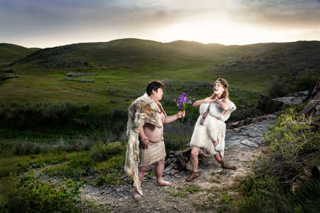 animal woman: Primitive caveman dressed in animal skin giving flowers to happy cave woman in the mountains