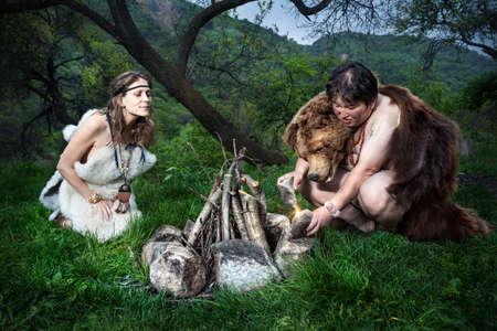 edad de piedra: cueva personas vestidos con piel de animal de hacer fuego en el bosque Foto de archivo