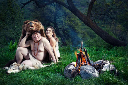 Cave people dressed in animal skin sitting near bonfire in the forest