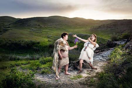 hombre prehistorico: hombre de las cavernas primitivo vestido con piel de animal regalar flores a la mujer de la cueva feliz en las montañas