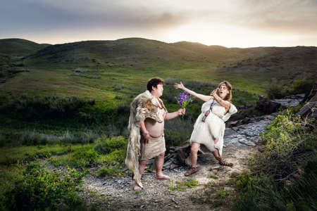 homo: Primitive caveman dressed in animal skin giving flowers to happy cave woman in the mountains