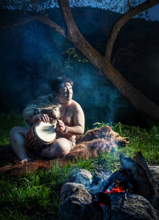 dweller: Caveman dressed in wolf skin playing drum near bonfire in the forest Stock Photo