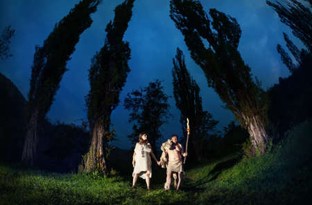 homo: Primitive people dressed in animal with torch light in the dark forest