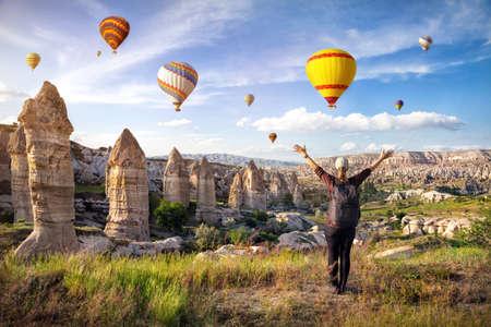 Jonge vrouw met rugzak op zoek naar zonsopgang hemel vol hete lucht ballonnen met opgeheven handen in Cappadocië, Turkije Stockfoto