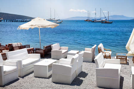 turkey beach: White sofa and table on the beach at seaside restaurant in Bodrum, Turkey Stock Photo