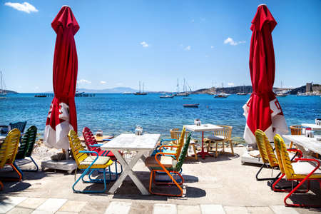 waterfront: Colorful chairs and white table in seaside restaurant in Bodrum, Turkey Stock Photo