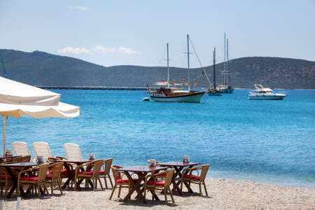 turkey beach: Cute chairs and table on the beach at seaside restaurant in Bodrum, Turkey Stock Photo