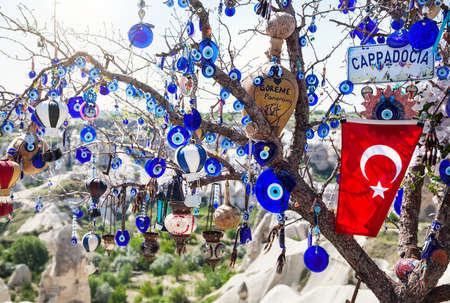 evil eyes: Evil eyes, balloon and Turkish flag on the tree in Goreme panorama Cappadocia, Turkey Stock Photo