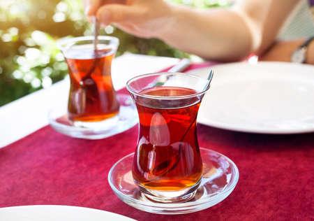トルコの赤いテーブルの上の伝統的なガラスのレストランでトルコの紅茶 写真素材
