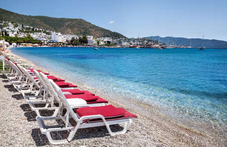 turkey beach: White sunbeds with red cover on the beach in Bodrum, Turkey Stock Photo