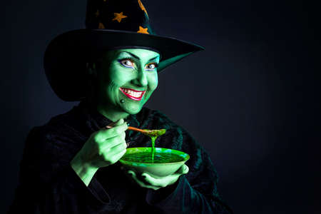 Witch with green skin holding plate with poison soup pumpkin at dark background