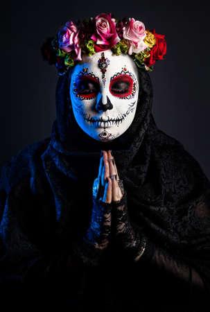 azucar: Muchacha con el cráneo del azúcar compone con las flores en fondo negro