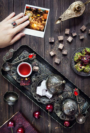 tea lamp: Turkish delights rahat lokum, tea in vintage dish, Aladdin lamp and woman hand holing photo with glowing lanterns in Istanbul