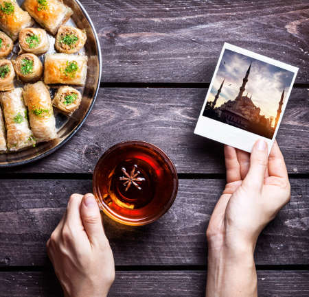 Hands with photo of Blue mosque in Istanbul and black tea near Turkish baklava on wooden background photo