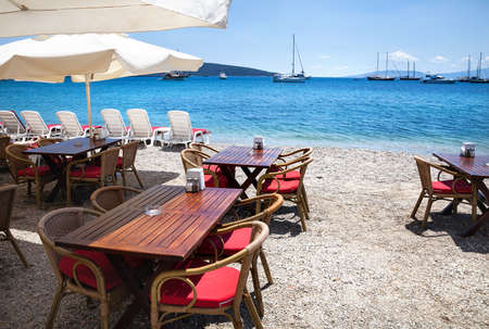 restaurant tables: Wooden chairs with tables on the beach at seaside restaurant in Bodrum, Turkey