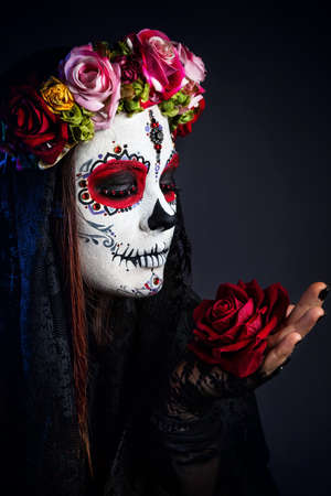 Girl with sugar skull make up with rose flower celebrating Day of the Dead at black background Stock Photo