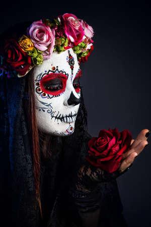Meisje met schedel suiker make-up met roze bloem vieren Dag van de Doden bij zwarte achtergrond