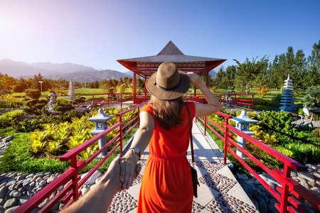 Mujer en traje y sombrero de color naranja holding hombre con la mano va a Jardín japonés con la pagoda Foto de archivo