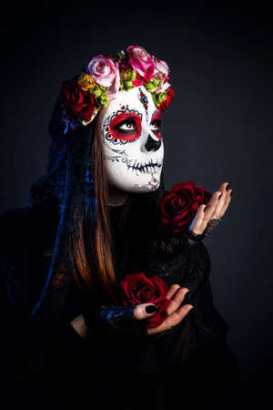 Girl with sugar skull make up with rose flowers celebrating Day of the Dead at black background
