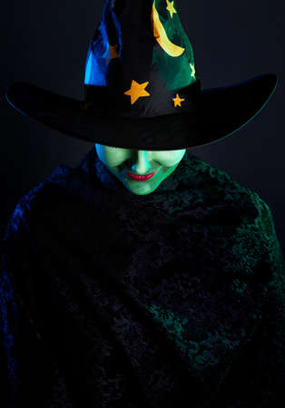 Witch with green skin in magic hat at Halloween on the dark background photo