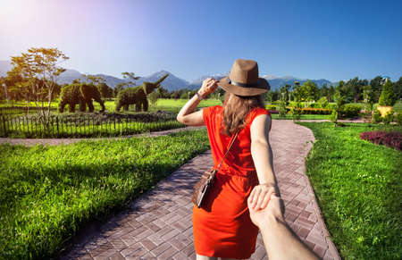 Woman in orange dress and hat holding man by hand and going to Topiary Garden with elephants