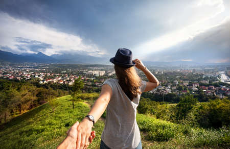 Woman in gray t-shirt and hat holding man by hand and looking to the city view in the mountains at dramatic sky