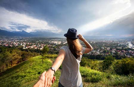 Vrouw in grijs t-shirt en hoed bedrijf man met de hand en op zoek naar het uitzicht op de stad in de bergen op dramatische hemel