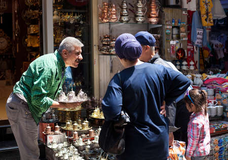 souvenir: ISTANBUL, Turkey - MAY 23, 2016: Turkish seller talking with customer in houseware shop. The Grand Bazaar is one of the largest and oldest covered markets in the world