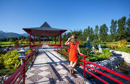 Woman in orange dress with hat looking to the Japanese Pagoda