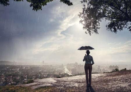 siluetas de mujeres: Silueta de la mujer con el paraguas de la calle con vista al panorama de la ciudad en la dramática noche lluviosa. , Época de estilo retro.