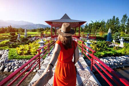 Donna in abito e cappello arancione che tiene l'uomo a mano andando a giardino giapponese con pagoda Archivio Fotografico - 60232466