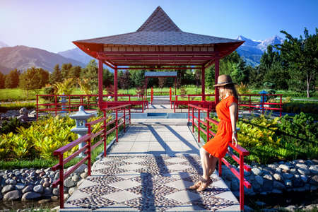Woman in orange dress and hat standing near the pagoda in Japanese Garden Stock Photo