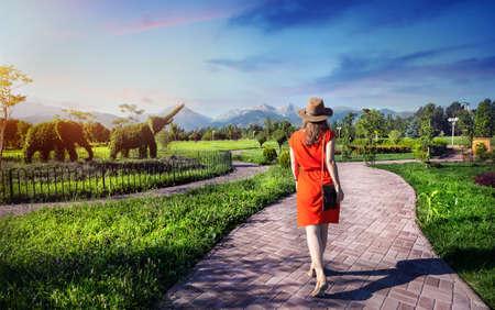 Mujer en traje de color naranja caminando por la carretera en Topiary del jardín con los elefantes de plantas