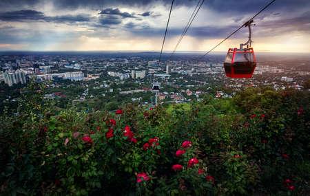 personas en la calle: Cabina roja del teleférico y jardín de rosas en vista a la ciudad en el fondo de cielo dramático atardecer tormentoso Foto de archivo