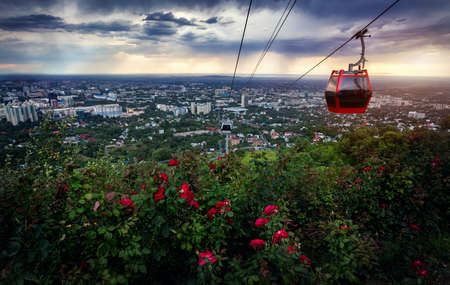 street people: Red cabin of cable car and rose garden at city view at dramatic stormy sunset sky background Stock Photo